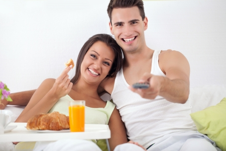 Smiling young couple spending free time together in bed  photo