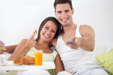 desayuno romantico: Sonriente joven pareja pasar el tiempo libre juntos en la cama