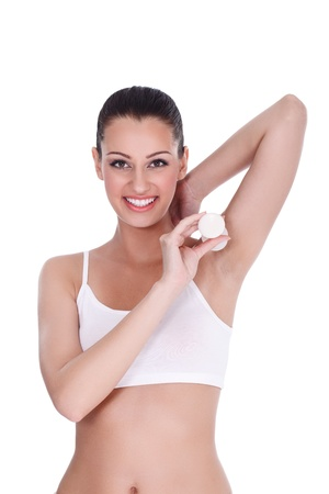 Young woman applying deodorant under armpit photo