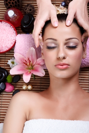 body spa:  Close up portrait of a young woman with eyes closed receiving facial massage Stock Photo
