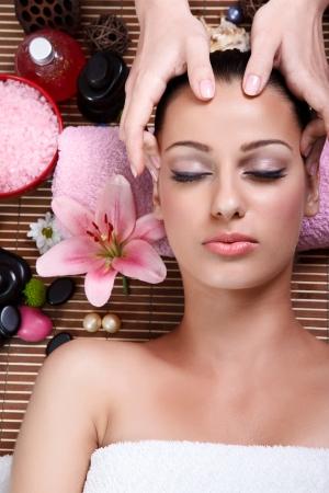 massaggio: Close up ritratto di una giovane donna con gli occhi chiusi che riceve il massaggio del viso