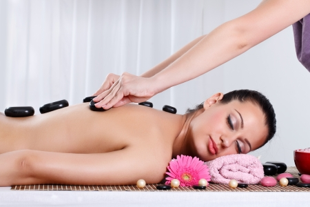 therapist: Beautiful woman receiving hot stone massage at spa and wellness center
