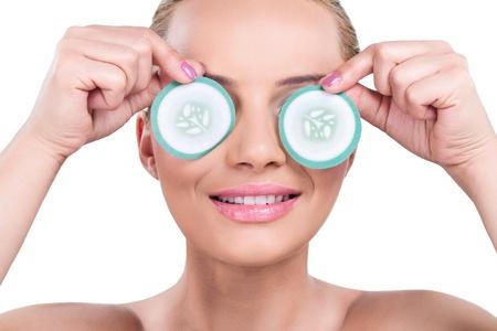 tratamientos corporales: mujer con rodajas de pepino sobre los ojos