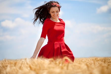 Beautiful young woman running through a wheat field in summer day photo