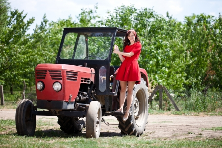 Young attractive girl on tractor, country life  photo