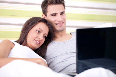 Young couple using laptop in bed photo