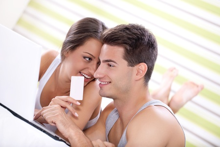 young couple shopping online in bedroom  photo