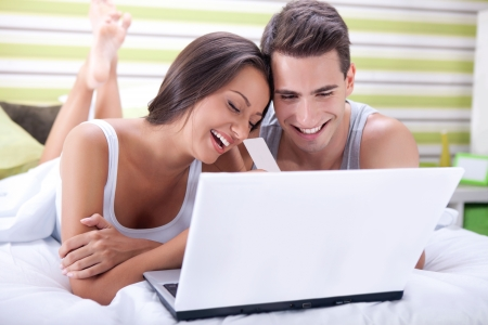 Couple with credit card buying on-line with a laptop in bed photo