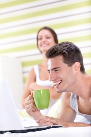Smiling couple having fun with laptop in bedroom photo