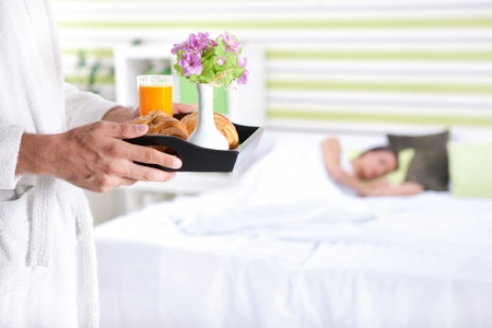Breakfast in bed, young man bringing breakfast in bed with his girlfriend photo