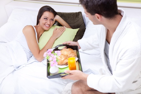 bed and breakfast: Portrait of happy young man serving breakfast for his girlfriend in bed at home