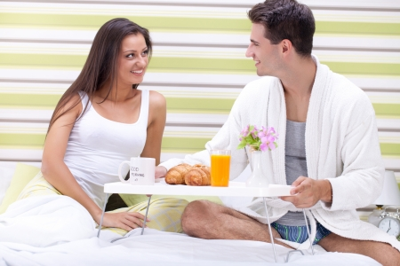 Young smiling couple having luxury breakfast in bed photo