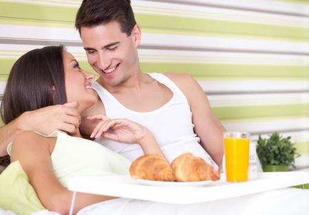 desayuno romantico: Pareja alegre joven de desayunar en la cama