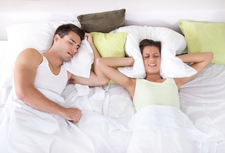 Couple in bed; man snoring and woman can not sleep; covering ears with pillow for snore noise.