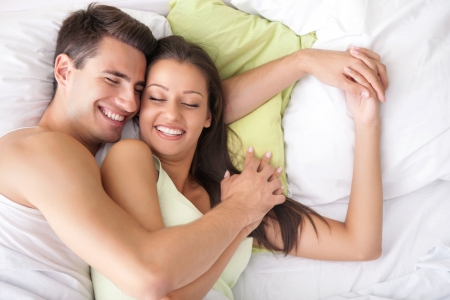 bed sheet: Lovely couple hugging on their bed at home Stock Photo