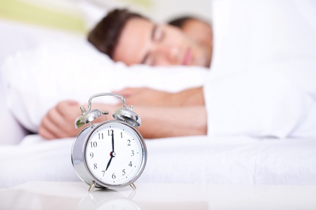 Young couple lying in white bed with silver alarm clock Stock Photo