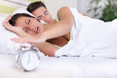 Upset woman turn off alarm clock, Wake up early morning. photo