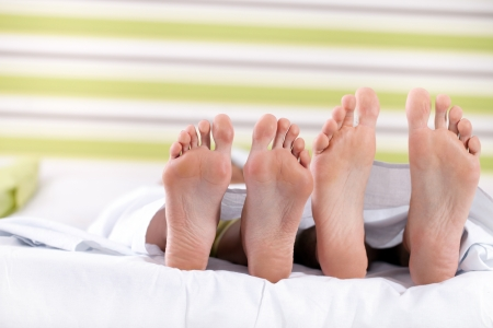 pair of feet on  the bottom of the bed,  protruding below sheets photo