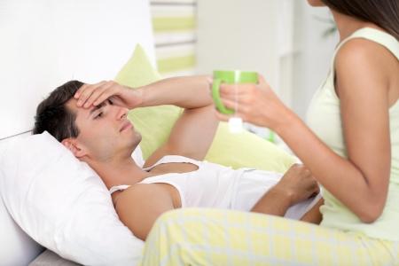 illnesses: Hombre enfermo con fiebre en la cama con chica temperatura cuidar para �l