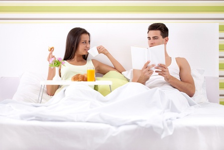 pareja en la cama: pareja de j�venes que domingo por la ma�ana en la cama