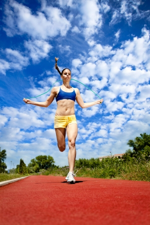 young sporty woman running and jumping rope, workout photo