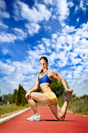 Young woman stretching before running on sport track photo