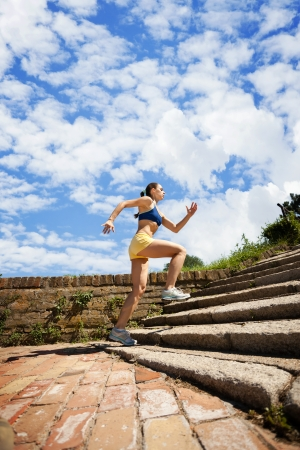 cardio workout: Young woman jogging in nature on steps  Stock Photo