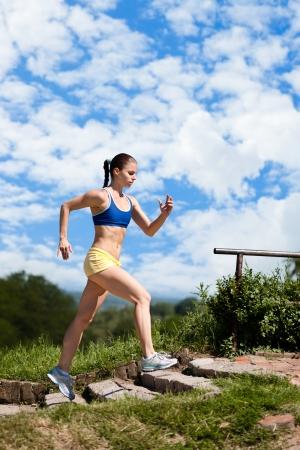 kardio: Sportos fiatal nő fut fel a lépcsőn a parkban