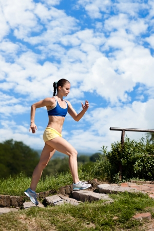 cardio fitness: Sporty young woman running up stairs in park