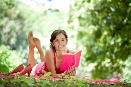 Reading  Woman reading book in park during spring   summer time  Happy smiling beautiful young university student studying lying down in grass   photo