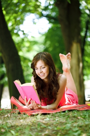 Woman reading book in park during spring or summer time  photo
