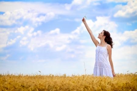 cornfield: Young beautiful woman in golden wheat field in summer