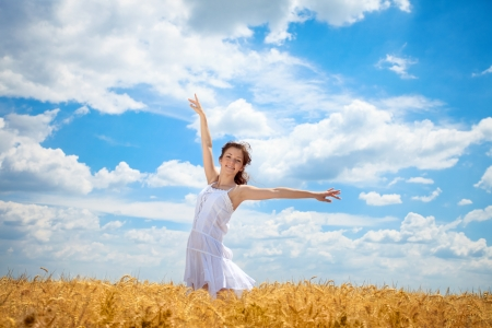 outstretched arms:  Young woman standing in wheat field with arms outstretched