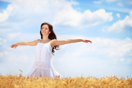 Young woman having joy in  golden wheat field photo