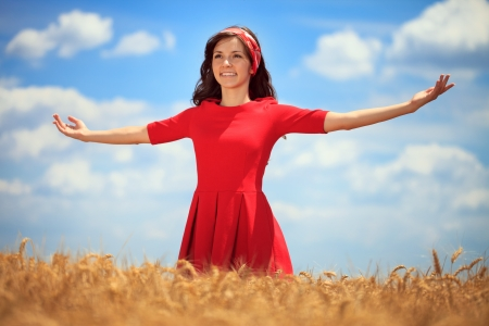 Young woman with hands raised up in the wheat field over blue sky in summer photo