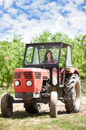 Young country girl driving tractor photo