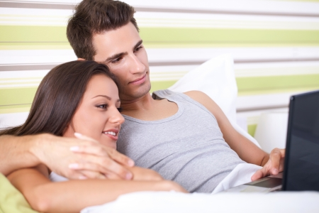 Affectionate young couple using a laptop lying on their bed photo