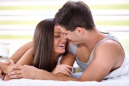 enamorados besandose: Amor pareja bes�ndose en la cama y mirando el uno al otro Foto de archivo