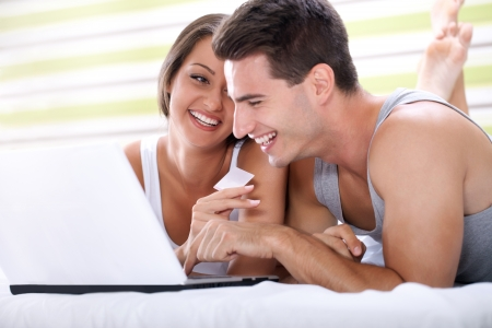 smiling couple shopping on line with credit card from bedroom  photo
