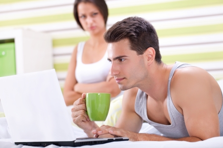 Man at computer, women upset and angry looking at man. Young modern interracial couple in bed. photo