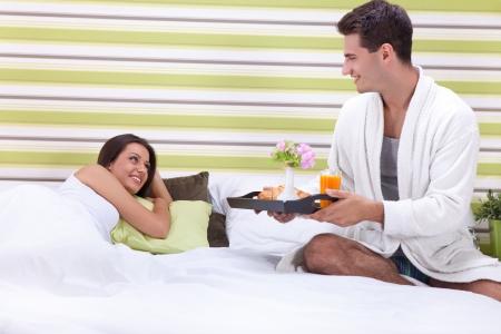desayuno romantico: El hombre que sirve a las mujeres un rom�ntico desayuno en la cama. Foto de archivo