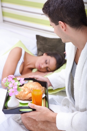 Man bringing the breakfast his girlfriend to in bed photo
