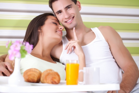Lovely young couple having breakfast in bed photo