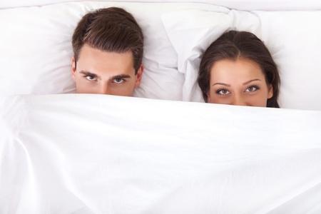 pareja en la cama: Divertido pareja acostada en la cama con la s�bana por encima de sus narices