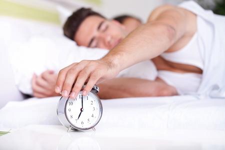 sleepy man:  guy turning off alarm clock