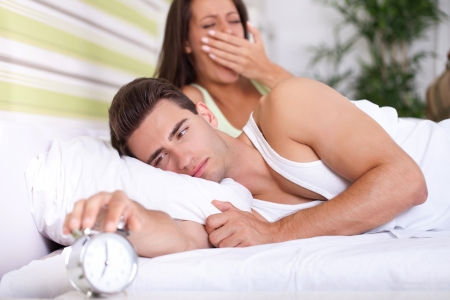 Couple in bed waking up, the men switches off the alarm clock photo
