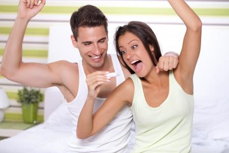 prueba de embarazo: joven pareja feliz con la prueba de embarazo en el dormitorio