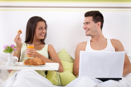 Young  couple sitting on bed and smiling, woman having breakfast and man using laptop photo