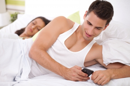 Cheating his wife, young men chatting with his mistress while his wife sleeps photo