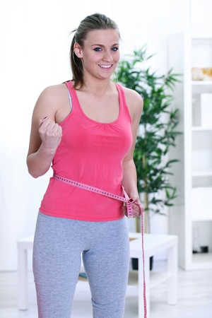 weight loss woman smiling happy excited standing with measuring tape  photo